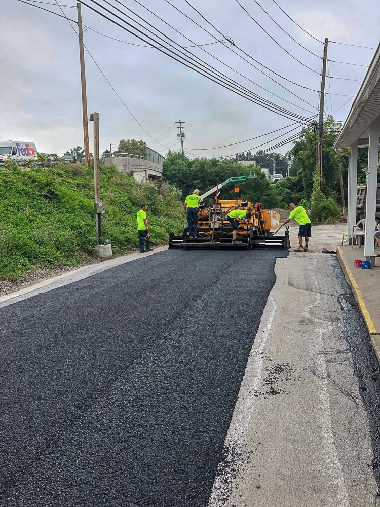 CMI Paving professionals pave an asphalt road as part of a commercial paving project