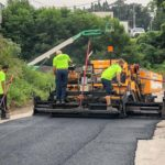 CMI paving professionals lay down asphalt on a roadwork job