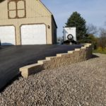 Asphalt driveway paved in front of a shed with a slope and gravel