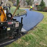 CMI Paving professionals work on paving a residential asphalt driveway